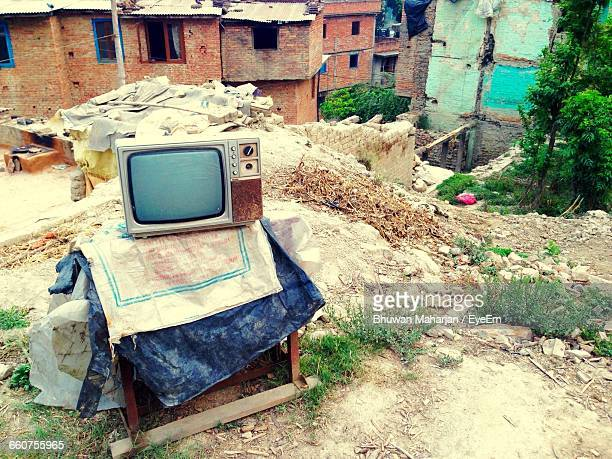 Old Television Set In Front Of Ruined Buildings
