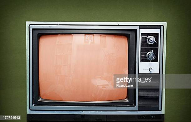 Old television set on a green background