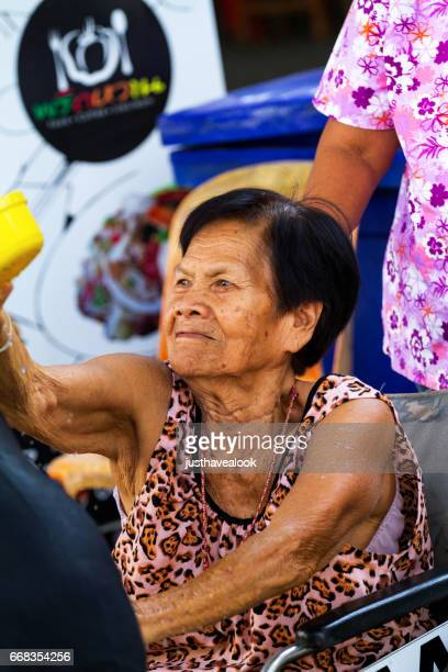 old thai senior woman in wheelchair play songkran - städtische straße stock pictures, royalty-free photos & images