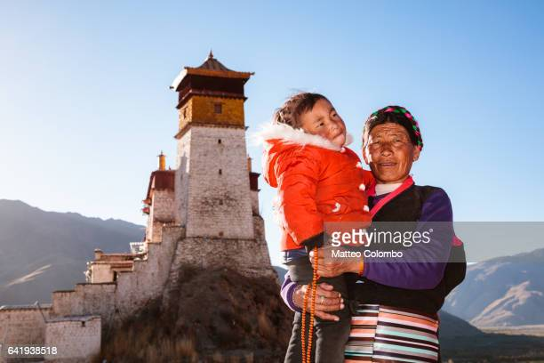 Old tibetan woman and child in traditional dress, Tibet