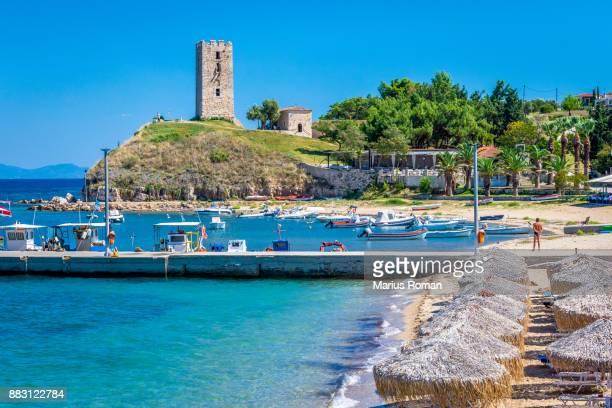 old tower, warf and beach, nea fokea, kassandra, halkidiki, greece. - peninsula de grecia fotografías e imágenes de stock