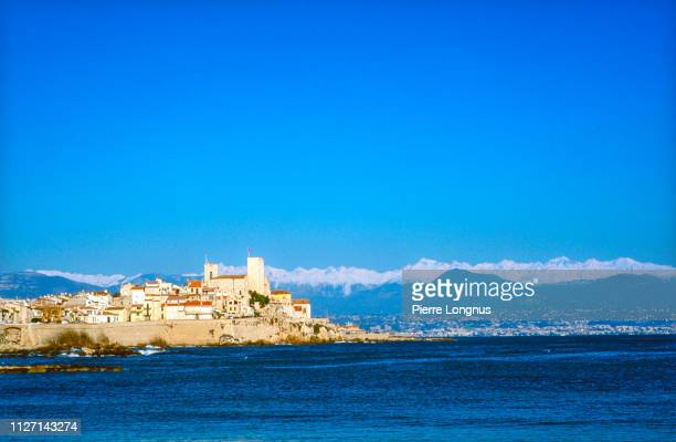 old town of antibes surrounded by the mediterranean sea, snow covered alps in the backdrop - antibes stock photos and pictures