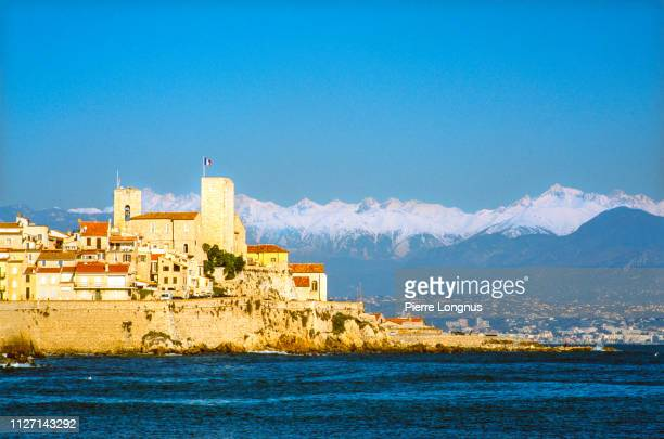 old town of antibes surrounded by the mediterranean sea, snow covered alps in the backdrop - alpes maritimes stock pictures, royalty-free photos & images