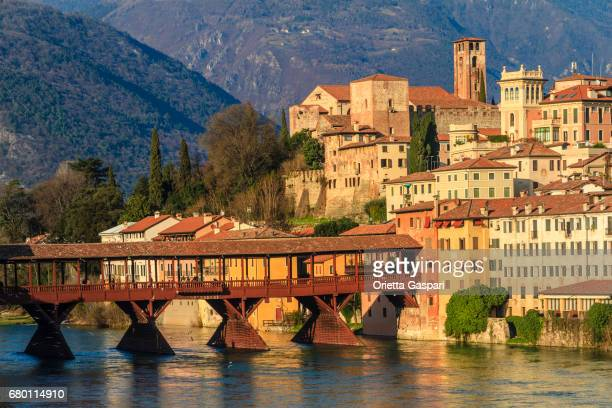 old town of bassano del grappa along the river brenta with the famous ponte degli alpini. province of vicenza, italy - véneto imagens e fotografias de stock