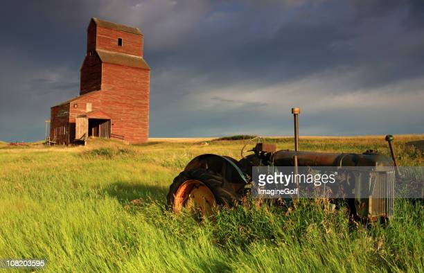 Old tractor and grain elevator on farm