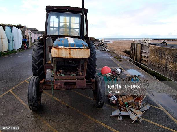 Old tractor used to pull boats out of the sea on the quay at Bude harbor, Cornwall, UK
