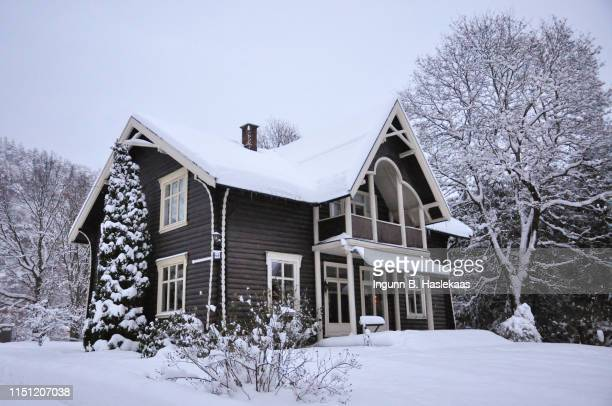 old traditional log house and family home in winter afternoon and snow. still some parts of summer outdoor furniture  on the porche. indoor light in the living room. - telemark stock pictures, royalty-free photos & images