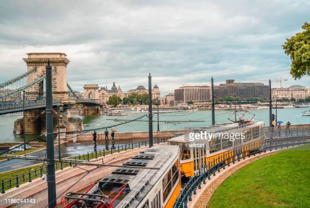 o bonde velho está indo perto da ponte chain no rio de danúbio em budapest - ponte széchenyi lánchíd - fotografias e filmes do acervo