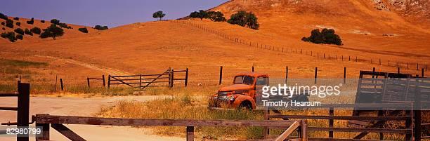 old truck in farmyard behind gate - timothy hearsum stock-fotos und bilder