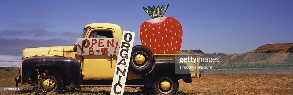 Old truck with giant strawberry : Stock Photo