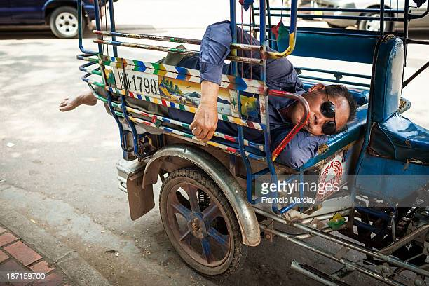 Old tuk-tuk driver sleeping on the back seat of his auto rickshaw during a hot afternoon in Vientiane, the capital city of Laos.