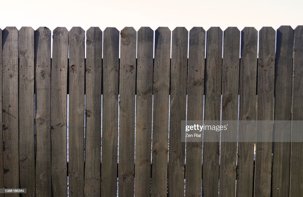 Old unpainted wooden picket fence against white background : ストックフォト