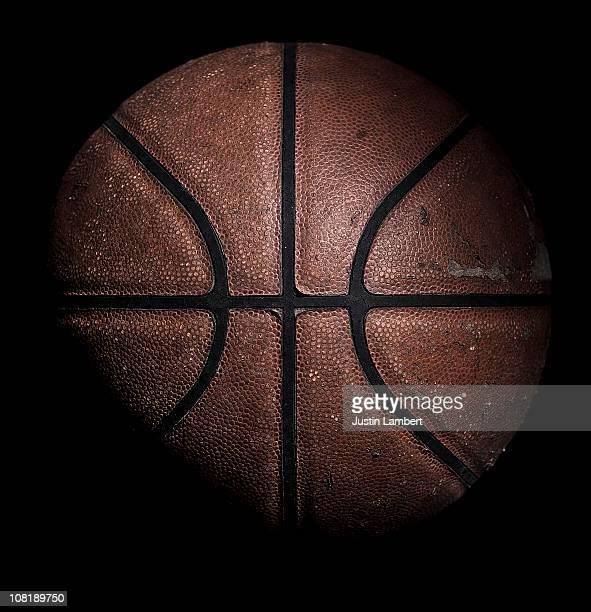 Old used basketball on black