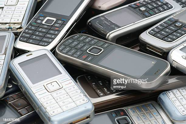Old used cellphones pile as background