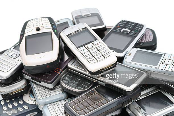 old used cellphones pile close-up isolated on white - former stock pictures, royalty-free photos & images