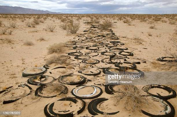 old, used tires form a roadway in the desert sand; mountains and clouds beyond - timothy hearsum stock pictures, royalty-free photos & images