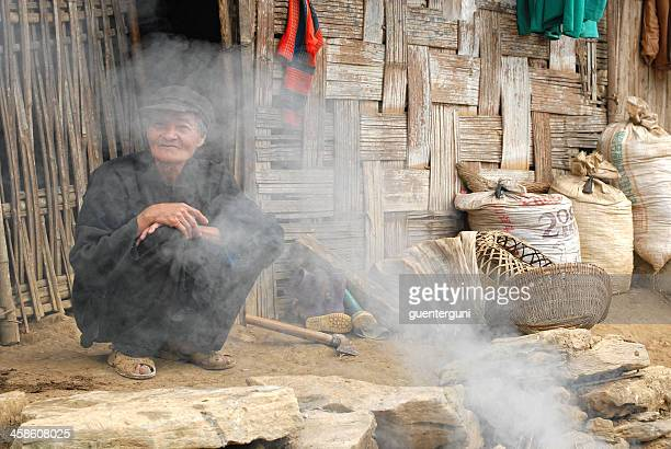 old vietnamese man is sitting at the fire place