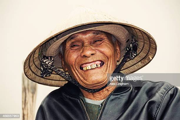 old vietnamese man with conical hat and gold teeth - gold tooth stock photos and pictures
