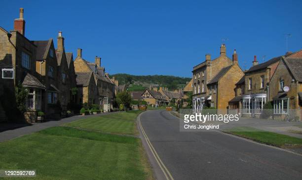 old village high street with houses and shops under blue sky - village stock pictures, royalty-free photos & images