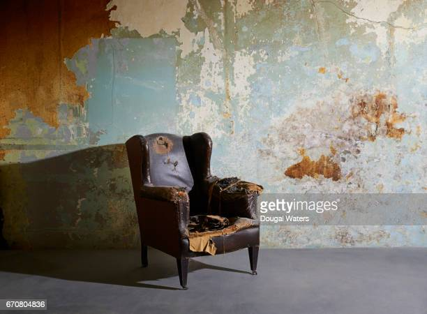 Old vintage arm chair in decaying room with paint peeling from wall.