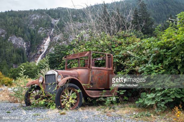 Old vintage car overgrown by bushes in Squamish, Canada