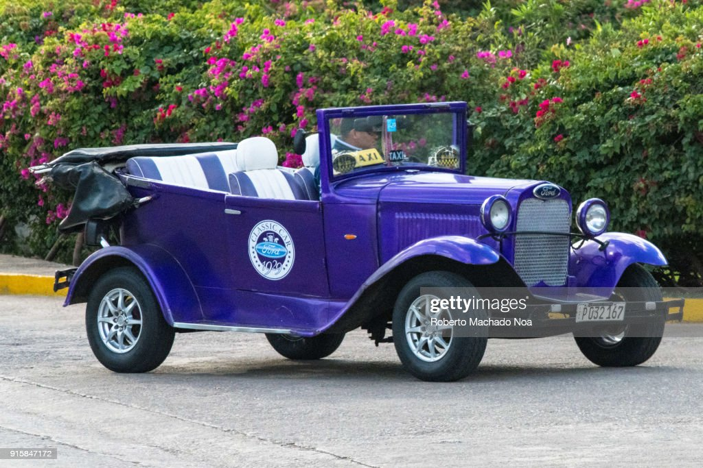 Old vintage cars in action. The blue Ford drives in the ...