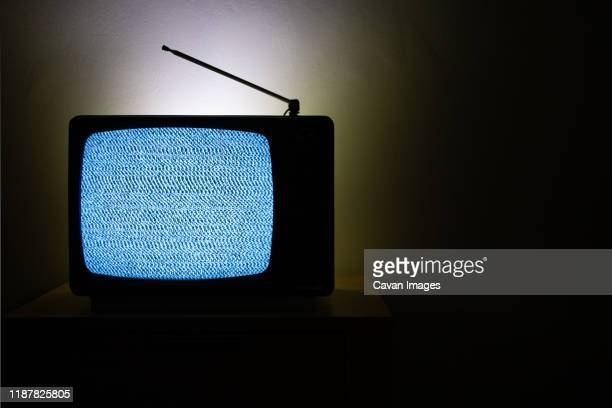 old vintage television isolated on dark background with no signal and grainy noise - kanaal stockfoto's en -beelden
