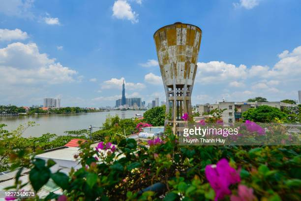 old water tower and landmark 81 building with bougainvillea view - saigon river stock pictures, royalty-free photos & images