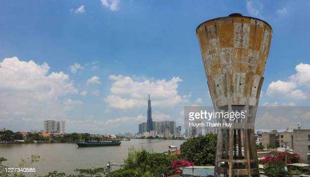 old water tower and landmark 81 by sai gon river - saigon river stock pictures, royalty-free photos & images