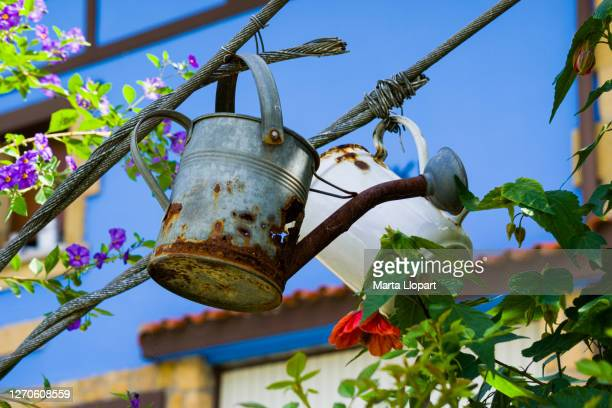 old watering can house garden with
