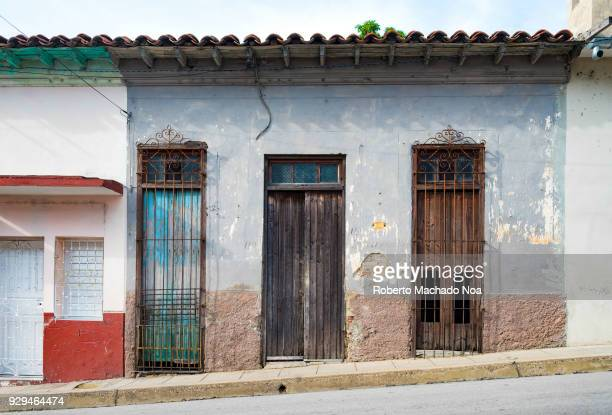 Old weathered house on a hill The building has clay tiles roof and wooden doors The vintage structure is typical of the past Cuban architecture