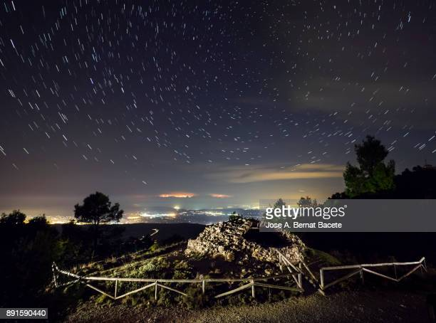 Old well or snow-storming tower of medieval architecture, located on top of a mountain, a night with the starry sky and a landscape of high mountain with the lights of the cities and the stars, with the north star. Valencian Community, Spain.