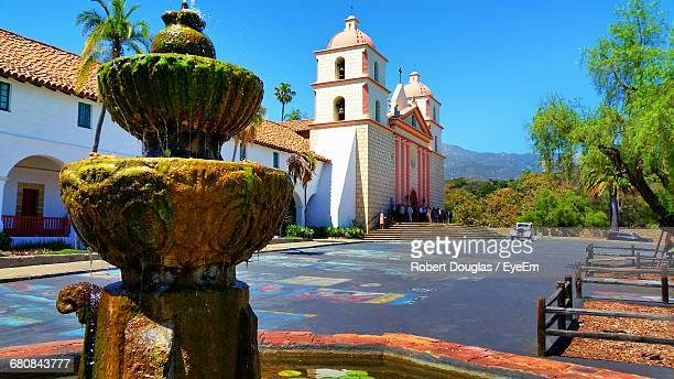 old wet moss covered fountain by mission santa barbara against clear sky - santa barbara stock photos and pictures
