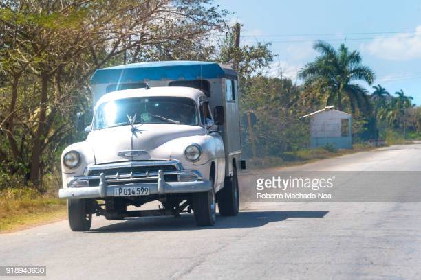 Old white Chevrolet car pulling a trailer that seems prepared for the transportation of more passengers