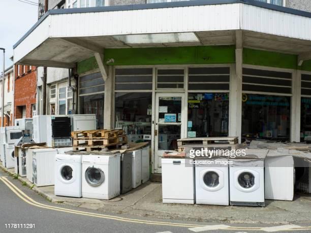 Old white goods outside shop, Holsworthy, Devon, UK.