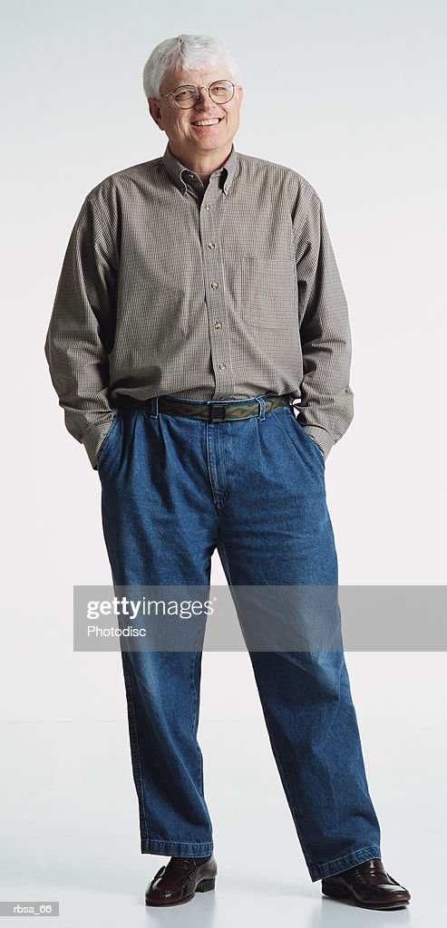 old white haired adult caucasian male with glasses wearing jeans and a gray shirt stands with hands in pockets and smiles pleasantly at the camera : Foto de stock