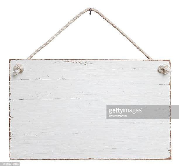 Old, white weathered signboard hanging by a string