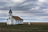 Old White Wooden Church in Rural Field Scene with Storm