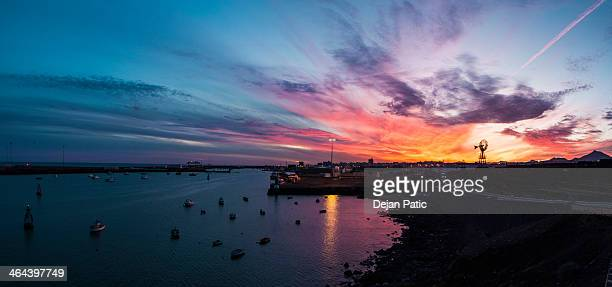 old windmill in spectacular sunset sky - arrecife stock photos and pictures