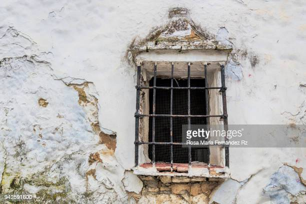 Old window of an abandoned house in the countryside, with a rusty grille, Andalusia, Spain.
