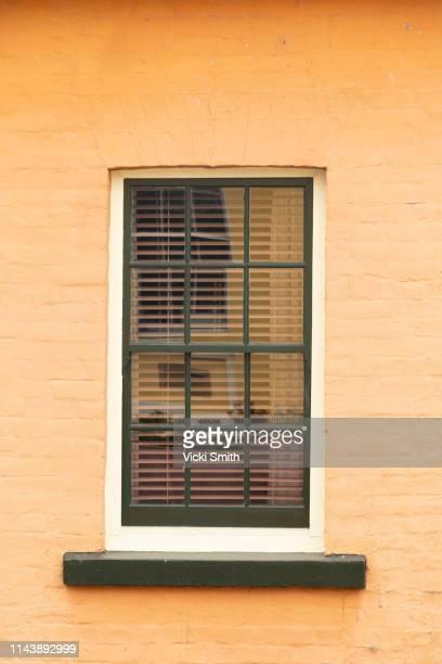old window set into a stone wall - altbau fassade stock-fotos und bilder