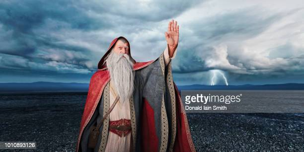 old wizard with long white beard raises hand with storm and lightning in background - wizard stock pictures, royalty-free photos & images