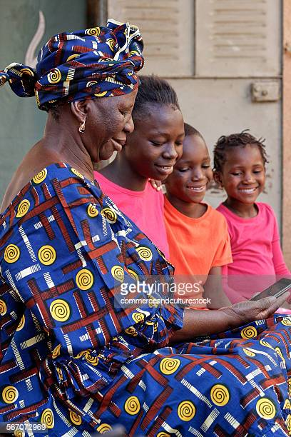 Old woman and children with a mobile phone