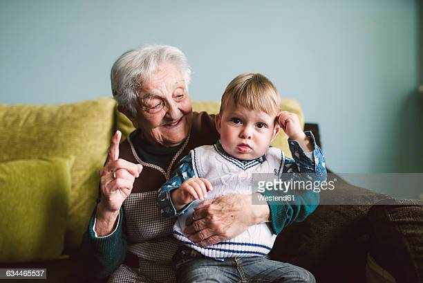 Old woman and her great-grandson sitting on the couch
