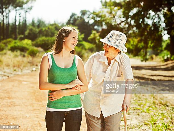Old woman and young granddaughter or caregiver enjoy forest walk