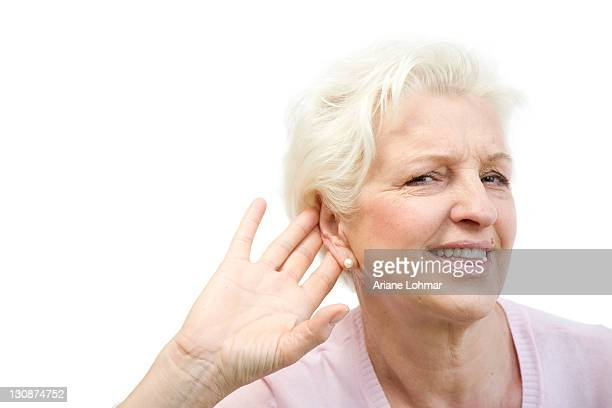 Old woman can't hear something, puts hand behind her ear