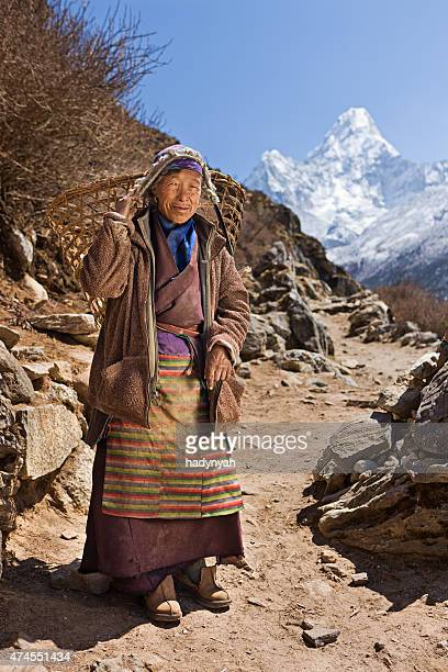 Old woman carrying basket in Himalayas