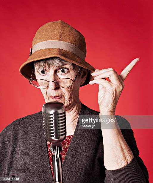 Old woman delivers lecture into microphone