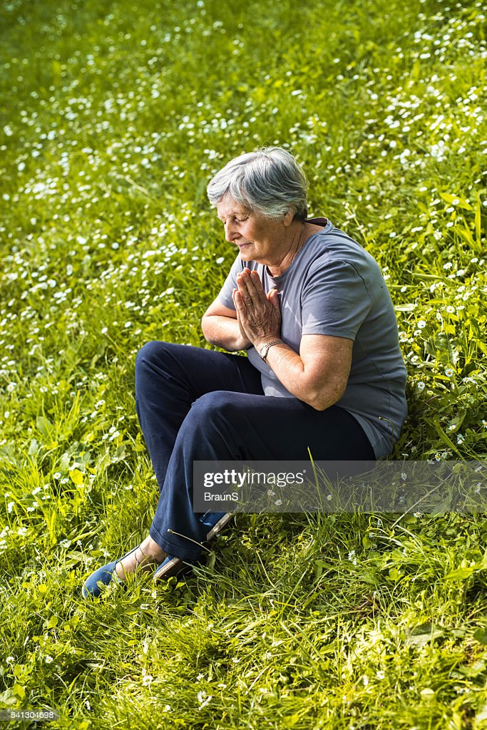Mature Woman Practicing Yoga Meditation On Forest Walkway