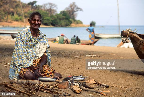 Old woman eating fish on the beach, Metangula, Niassa Province, Mozambique.